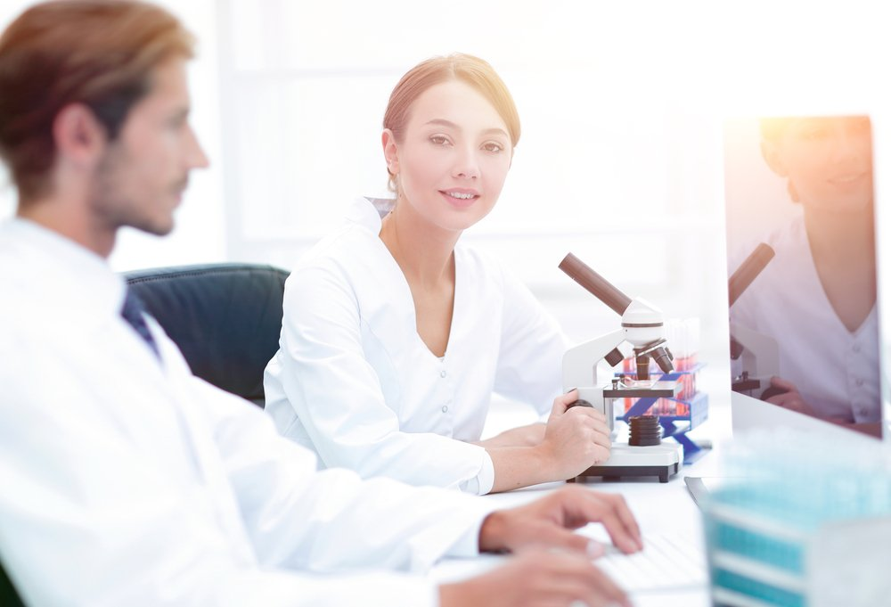 Portrait of confident female scientist with colleague in background at laboratory