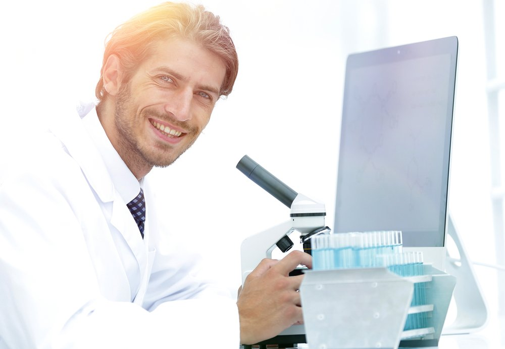 Side view of a male scientific researcher using microscope in the laboratory